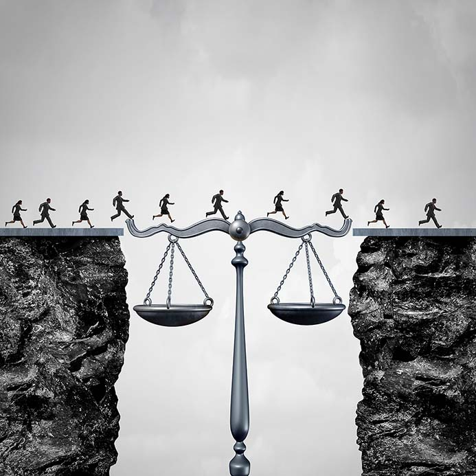 People walking across a gap bridged by the scales of justice