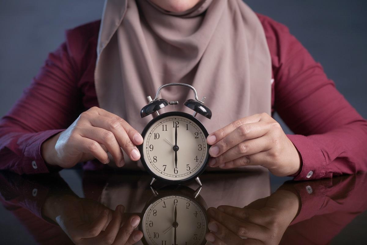 Muslim woman holding a clock.