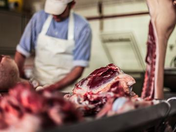 Butcher cutting raw meat with a knife at table in the slaughterhouse