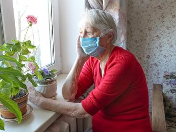 Old woman with a facemask looking out a window