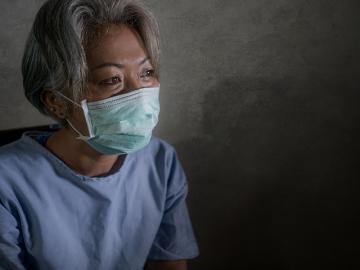 mature woman with grey hair in hospital patient gown and mask infected by COVID-19
