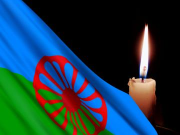 Roma flag against a burning candle