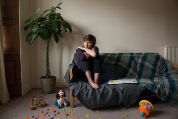 Woman sitting alone in a living room by a sofa