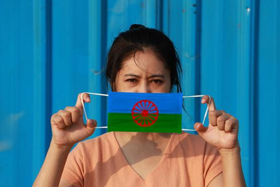 Roma woman with a facemask with a Roma flag on it