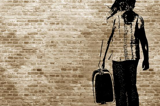 Graffiti/shadow on a brickwall showing a refugee girl walking with her suitcase