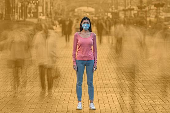 Woman in face mask alone in a crowded street