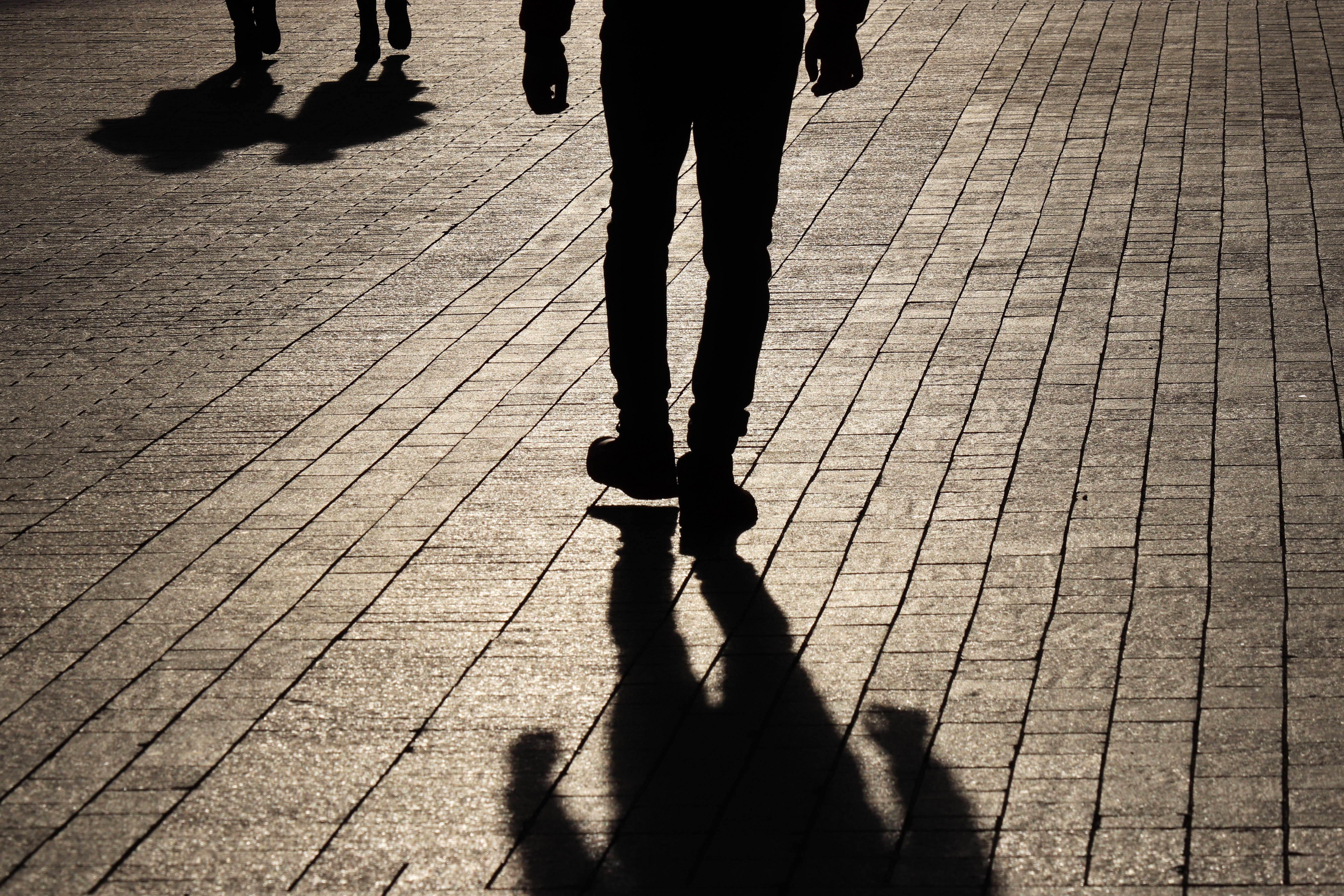 Shadow man walking towards a couple on a street