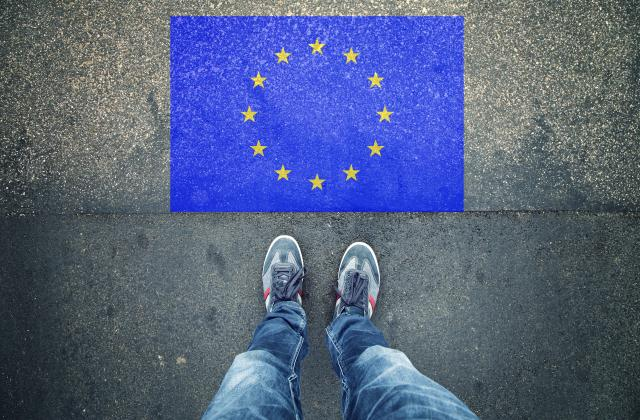 Feet standing of EU flag on pavement