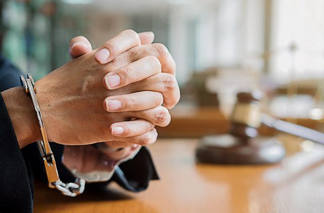 Hands clasped in handcuffs on desk with gavel in background