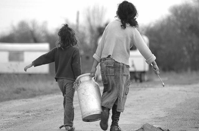 Two Traveller children carrying a container